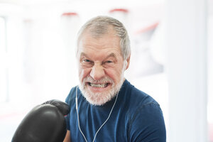 Portrait of aggressive senior man with earphones and boxing gloves in gym - HAPF01671