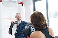 Fit senior woman boxing with her coach - HAPF01680