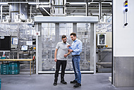 Two men with tablet talking in factory shop floor - DIGF02338
