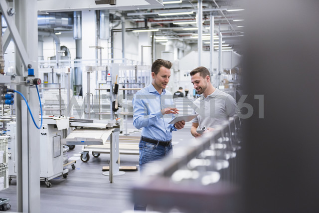 Two men with tablet talking in factory shop floor - DIGF02344 - Daniel Ingold/Westend61