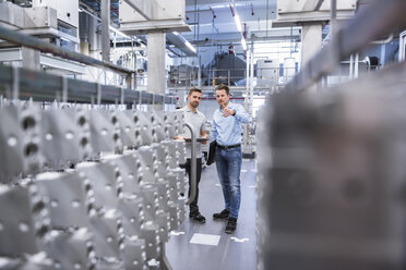Two men with tablet talking in factory shop floor - DIGF02353