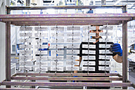 Man working in factory shop floor hanging products on rack - DIGF02359