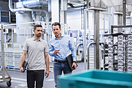 Two men walking and talking in factory shop floor - DIGF02362