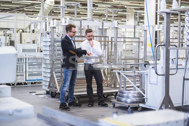 Two men talking in factory shop floor - DIGF02371 - Daniel Ingold/Westend61