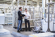 Two men talking in factory shop floor - DIGF02371