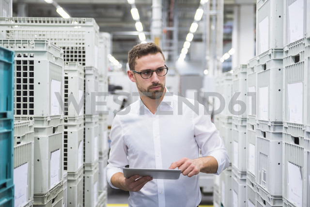 Man using tablet at boxes in factory shop floor - DIGF02374 - Daniel Ingold/Westend61