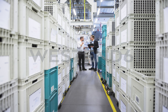 Two men with tablet talking at boxes in factory shop floor - DIGF02377 - Daniel Ingold/Westend61