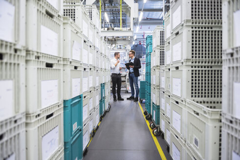 Two men with tablet talking at boxes in factory shop floor - DIGF02377