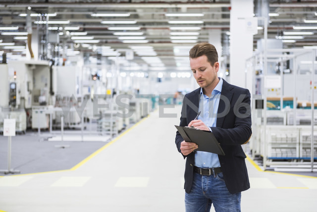 Man standing in factory shop floor taking notes - DIGF02383 - Daniel Ingold/Westend61