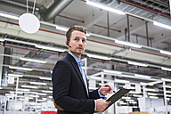 Man with headset in factory shop floor taking notes - DIGF02386