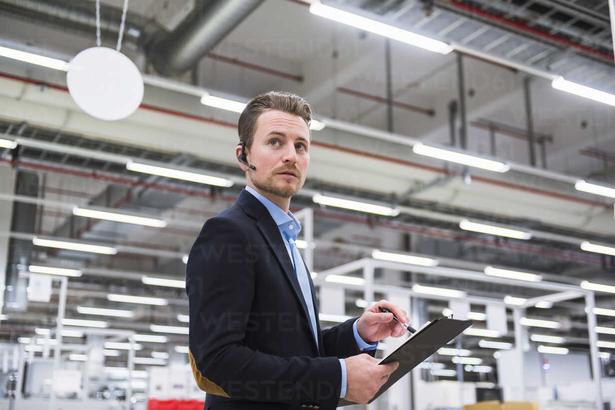 Man with headset in factory shop floor taking notes - DIGF02386 - Daniel Ingold/Westend61