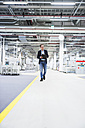 Man walking in factory shop floor taking notes - DIGF02389