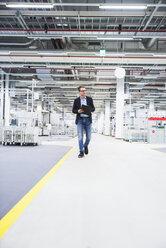 Man walking in factory shop floor taking notes - DIGF02389