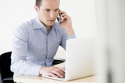 Businessman on the phone using laptop - FMOF00244