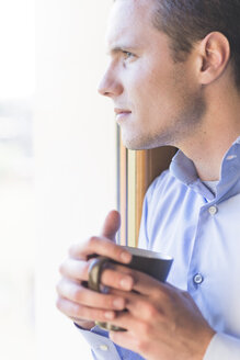 Businessman with cup of coffee looking out of window - FMOF00247
