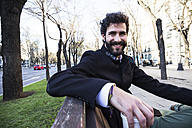 Portrait of smiling young man with full beard with coffee to go sitting on a bench - ABZF01995