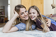 Portrait of happy little girl lying on the floor with her mother - TCF05394