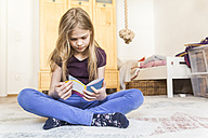 Girl sitting on the floor of children's room reading a book - TCF05397