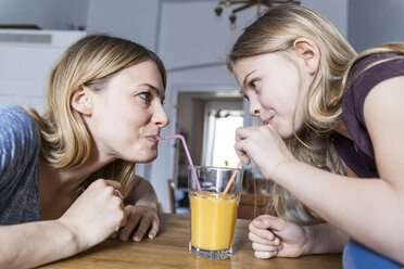 Mother and daughter sharing an orange juice in kitchen - TCF05400