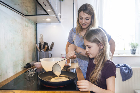 Mother and daughter baking pancakes in kitchen - TCF05403