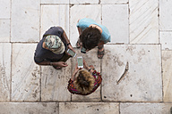 Overhead view of three people looking at cell phones - KKAF00775