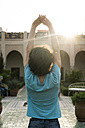 Morocco, Marrakesh, tourist stretching in a courtyard - KKAF00784