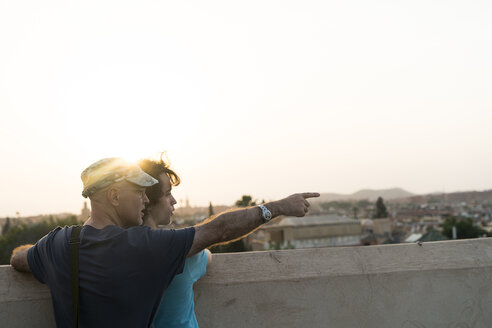 Morocco, Marrakesh, two tourists looking at the city at sunset - KKAF00793