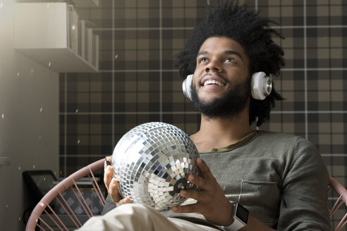 Man sitting in living room in armchair holding mirror ball listening to music - SBOF00378