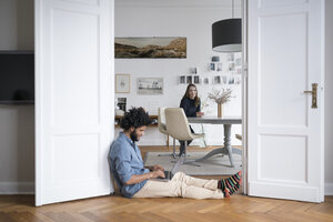 Man at home sitting on floor working with laptop with woman in background - SBOF00381
