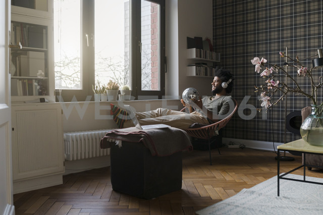 Man sitting in living room in armchair holding mirror ball listening to music - SBOF00384 - Steve Brookland/Westend61