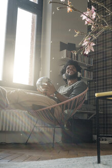 Man sitting in living room in armchair holding mirror ball listening to music - SBOF00387