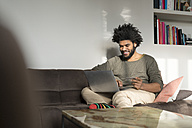 Man sitting on couch in living room with laptop and credit card - SBOF00393