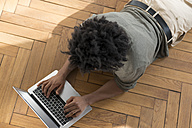 Man lying on floor working on laptop - SBOF00396