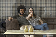 Smiling couple sitting on couch watching Tv - SBOF00399