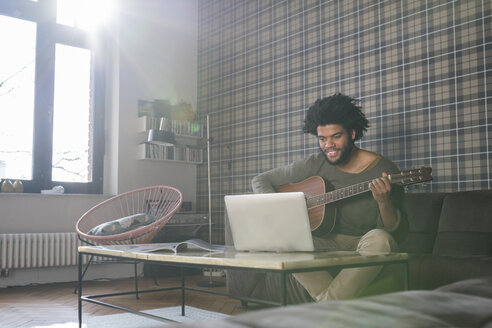 Man sitting in living room on sofa playing guitar in front of laptop - SBOF00402