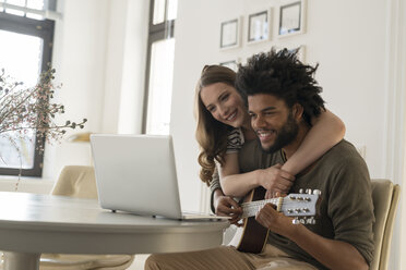 Smiling couple in front of laptop in living room, man playing guitar - SBOF00408