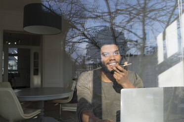 Man speaking on smartphone in front of laptop at the window - SBOF00417