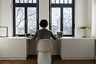 Man working in front of panorama window at home with laptop and tablet - SBOF00420