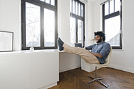 Man sitting in minimalist empty room on chair - SBOF00429
