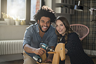 Smiling couple looking at camera mounting rocking horse with cordless drill - SBOF00438