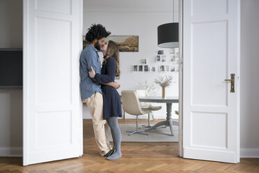 Kissing couple at home standing in door frame in living room - SBOF00441