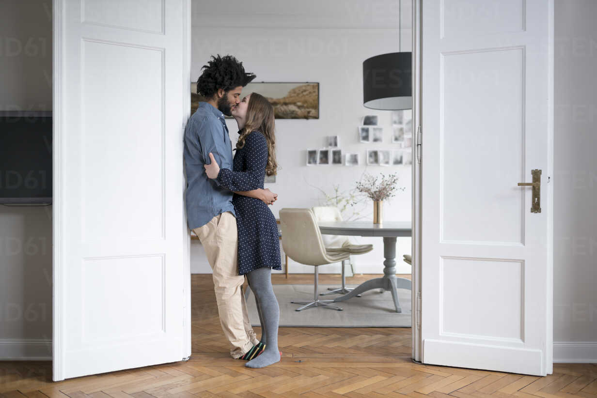 Kissing couple at home standing in door frame in living room - SBOF00441 - Steve Brookland/Westend61