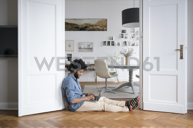 Man at home sitting on floor working with laptop in door frame - SBOF00444 - Steve Brookland/Westend61