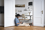 Man at home sitting on floor working with laptop in door frame - SBOF00444