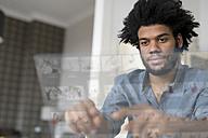 Man at home working on futuristic screen - SBOF00450