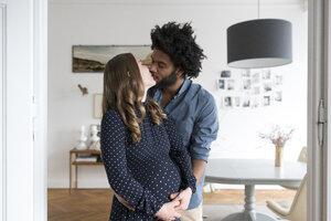 Kissing pregnant couple in living room - SBOF00456