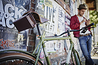 Germany, Hamburg, St. Pauli, Man using smartphone with bicycle in foreground - RORF00818