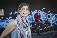 Germany, Hamburg, St. Pauli, Young woman and man on bicycle standing in front of graffiti - RORF00821