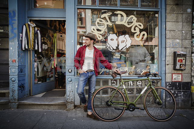 Germany, Hamburg, St. Pauli, Man with bicycle waiting in front of vintage shop - RORF00824 - Roger Richter/Westend61
