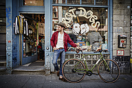 Germany, Hamburg, St. Pauli, Man with bicycle waiting in front of vintage shop - RORF00824